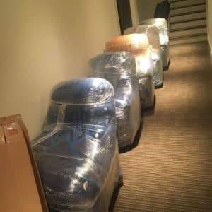 six lined up wrapped chairs in hallway